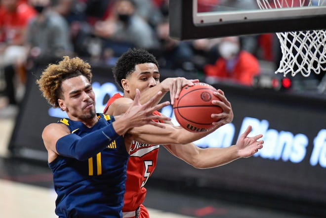 West Virginia's Emmitt Matthews Jr. (11) and Texas Tech's Micah Peavy (5) fight for a rebound during the first half of a Big 12 Conference game Tuesday at United Supermarkets Arena. [AP Photo/Justin Rex]