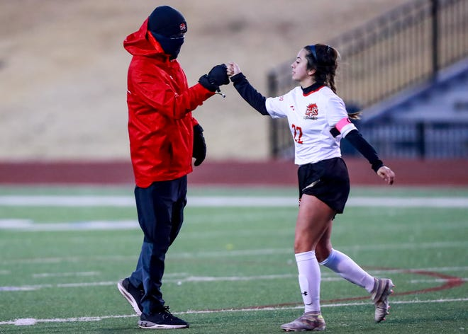 Coronado head coach Alistair Caldwell fist bumps Lexi De La Cruz (22) after the win against Monterey on Tuesday, Feb. 9, 2021, at Lowrey Field at PlainsCapital Park in Lubbock, Texas.