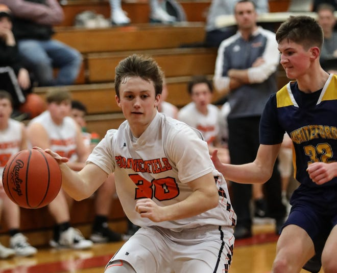 Summerfield's Brock Olmstead drives the baseline against Luke Rasor of Whiteford during a game last season. He hit 10 free throws in overtime and finished with 25 points as the Bulldogs won their season opener in triple overtime. [Photo courtesy of KENDRA DAFOE]