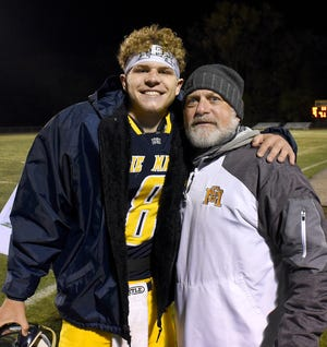 Rob Beaudrie (right) hugs his son Noah after an Erie Mason playoff victory this season. Beaudrie has resigned as Mason coach. [MONROE NEWS PHOTO BY TOM HAWLEY]