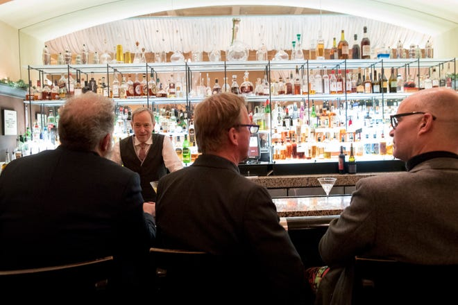 A bartender talks to a customer at the Gotham Bar and Grill in New York on Nov. 27, 2018. The Manhattan upscale restaurant hopes to reopen by summer 2021 if government regulations permit, but will likely have just 35 staffers instead of the 100 the restaurant had before it closed in March 2020. [AP Photo/Mary Altaffer]