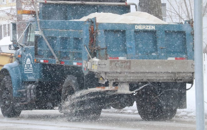 A City of Pontiac truck rolls along Water Street spreading salt Wednesday afternoon. The roads were getting slick as a light snow fell on Pontiac early Wednesday afternoon.
