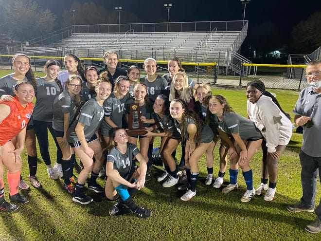 The Dwyer girls soccer team celebrates its Class 7A-District 9 championship. The Panthers beat Vero Beach 2-1.