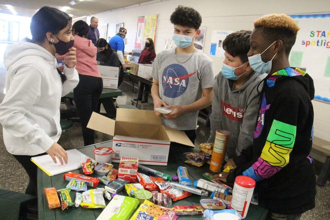 From left, Perry seventh-graders Sofia Martinez, Jacobo Cerna, Mosses Calderon and Misha Sarpee work together to sort and pack items for the care boxes.