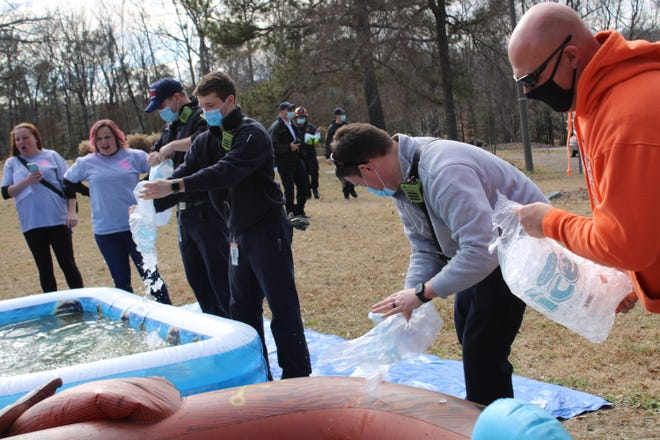 "Colonial Heights firefighters and police officers fill kiddie pools with ice for the ""Crazy Colonials"" Polar Plunge event at White Bank Park in Colonial Heights, Va. on Feb. 6, 2021."