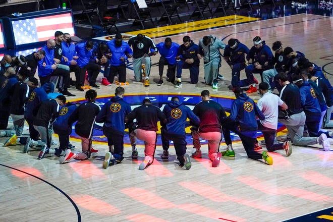 Members of the Denver Nuggets and the Dallas Mavericks lock arms and take a knee during the national anthem before the Jan. 7 game in Denver.