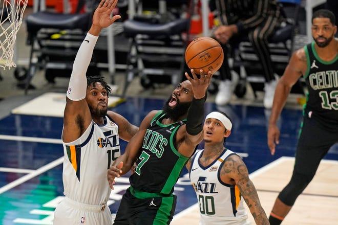 The Celtics' Jaylen Brown goes up for a shot against Utah Jazz center Derrick Favors, left, during the first half Tuesday night in Salt Lake City.