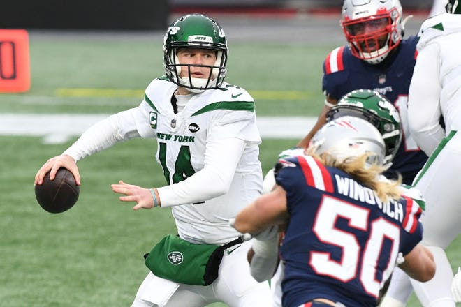 New York Jets quarterback Sam Darnold (left) looks to pass under pressure from New England Patriots defensive end Chase Winovich during the second quarter at Gillette Stadium this past season.