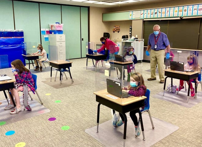 Students remain socially distanced from one another in the classroom, with plexiglass shields sitting on top of each desk.