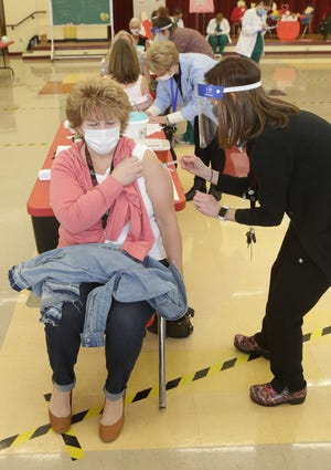 Andrea Johnsen, an elementary school nurse for the Canton City School District, administers the Moderna vaccine shot Wednesday to Linda Dillon Young, a speech therapist in the district. More than 800 Canton City school employees were vaccinated Wednesday at Lehman Middle School.