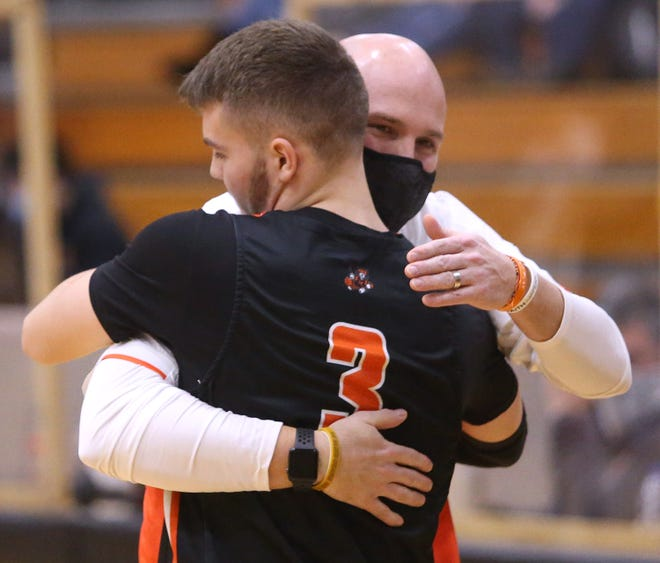 Josh Hose, Massillon head basketball coach, embraces Luke Sabo (3) during their game at Hoover on Tuesday, Feb. 9, 2021.
