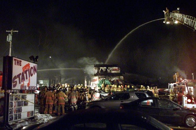 Firefighters spray water on to the charred remains of the nightclub, The Station on Feb. 20, 2003, in West Warwick, R.I. The nightclub fire killed 100 people.