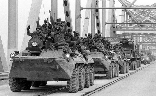 Soviet army soldiers wave their hands as their last detachment crosses a bridge on the border between Afghanistan and then Soviet Uzbekistan near the Uzbek town of Termez on Feb. 15, 1989, as they leave Afghanistan after waging a 10-year war in a failed attempt to impose Soviet rule in the country.