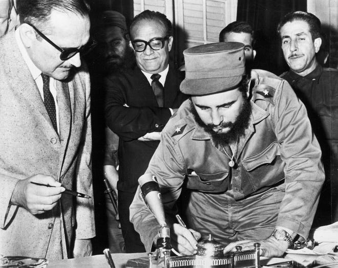 Cuba's revolutionary hero Fidel Castro, right, signs the Instrument of Office to become Prime Minister of Cuba, at a ceremony in Havana on Feb. 16, 1959. Cuban President Manuel Urrutia, left, waits to place his signature on the document.