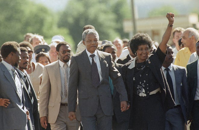 Nelson Mandela is led by his wife, Winnie Mandela, who gives a black power salute, after his release from Victor Verster prison in Cape Town, South Africa, on Feb. 11, 1990. The leader of the African National Congress served over 27 years in jail.