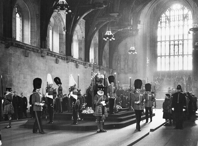 Members of the public pass the coffin of Britain's King George VI, as it lays in state, and the guard is changed in total silence, in Westminster Hall, London, on Feb. 13, 1952.