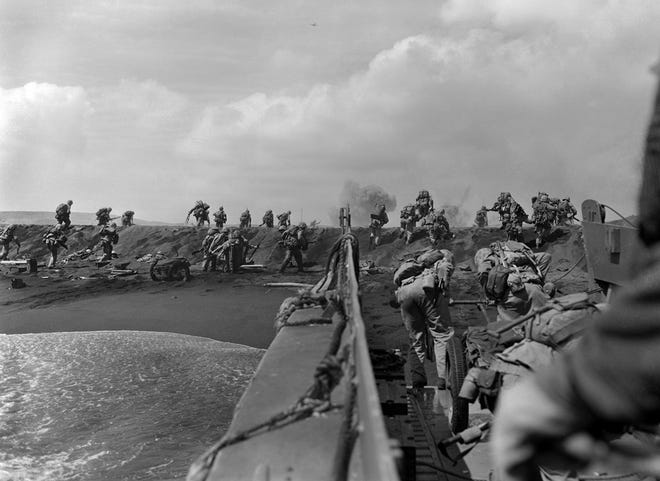 In the Pacific theater of World War II, U.S. Marines hit the beach and charge over a dune on Iwo Jima in the Volcano Islands Feb. 19, 1945, the start of one of the deadliest battles of the war against Japan.