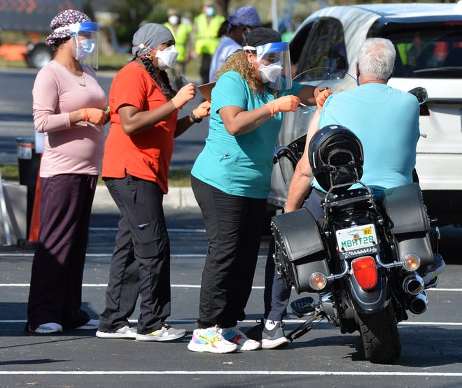 A motorcyclist gets a COVID-19 vaccine dose Feb. 10 during a pop-up clinic at the Venice Community Center. Other pop-up vaccine clinics in Charlotte County and Manatee County are drawing complaints of political favoritism.