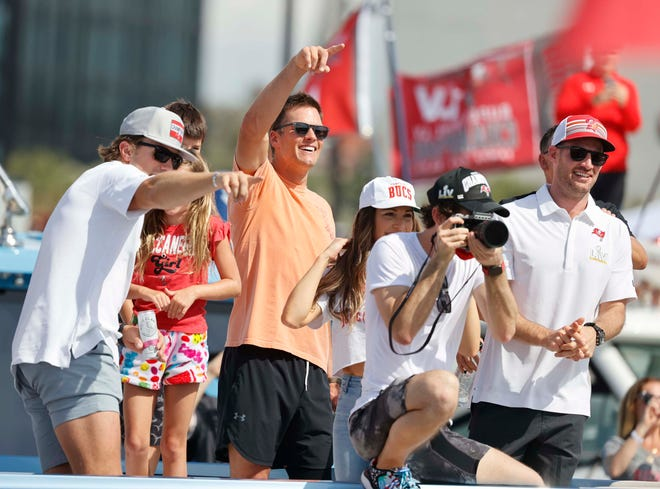 Tampa Bay Buccaneers quarterback Tom Brady, center, waves to the crowd during the boat parade Feb. 10 in Tampa celebrating the Bucs' victory over the Kansas City Chiefs in Super Bowl LV.