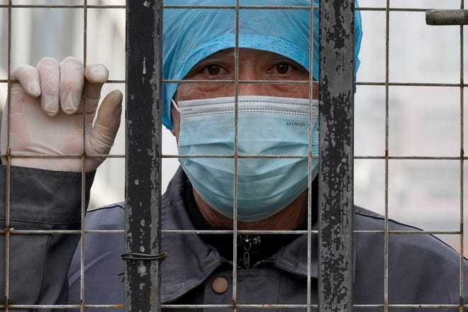 A worker wearing a mask, watches from inside a hospital across the Wuhan Center for Disease Control and Prevention after the World Health Organization team arrive to make a field visit in Wuhan in central China's Hubei province on Monday, Feb. 1, 2021. (AP Photo/Ng Han Guan)