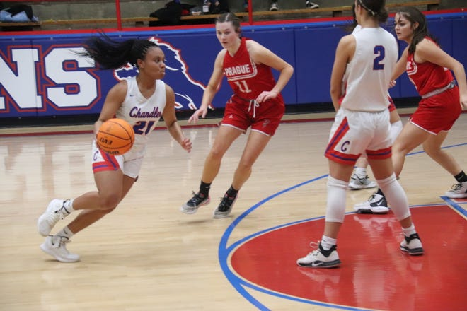 Chandler's Jaelynn Robertson (21) prepares to drive with the basketball toward the hoop as teammate Hannah Vandenbrand (2) sets a screen. Pictured for Prague is Mattie Rich (11).