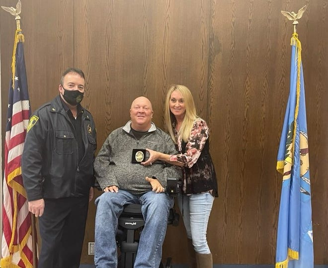 Shawnee Police Chief Mason Wilson, left, is pictured with Jeff Rodgers and his wife, Dawna, after presenting Rodgers with a corporal's badget.