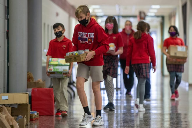 Christ The King Elementary School fifth-grader Miller Reid leads a group of students  Wednesday carrying items of food as part of a food drive for Project Topeka.