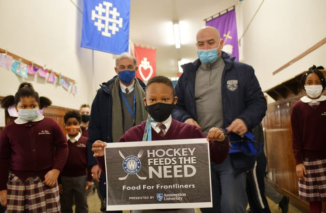 St. Peter's student Trevin Kinyanjui, 8, holds a banner for the program. Standing in background are Assumption College President Francesco C. Cesareo and Worcester Railers Chief Operating Officer Mike Myers.