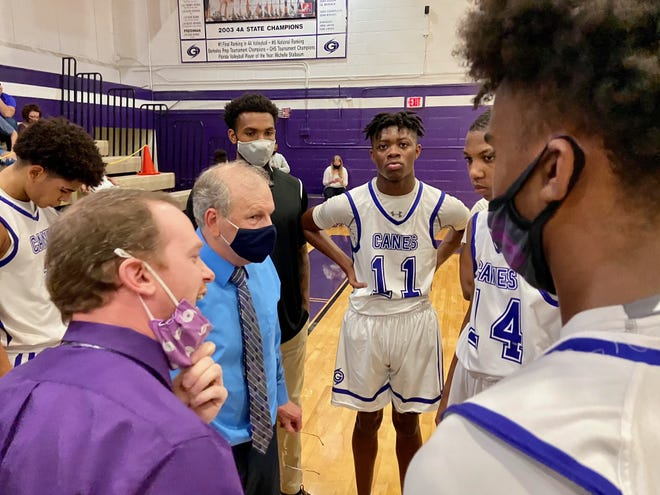Gainesville High coaches shout instructions to Hurricanes players during a fourth-quarter timeout Tuesday night.