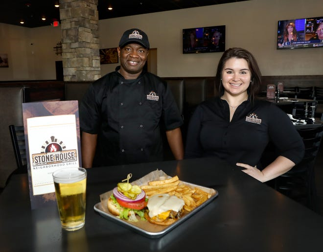 Stone House Neighborhood Grill chef Guerby Brazes, left, and Jamie Sulecki, the general manager, with the Hoss Burger at the new restaurant in Newberry.