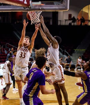 Elon forwards Simon Wright, left, and Hunter Woods, right, reach for a rebound against James Madison during Tuesday night's game at Schar Center.
