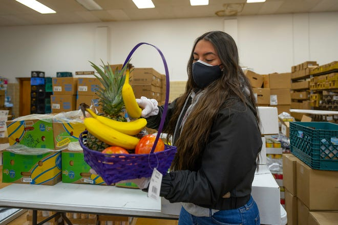 Lolo Elouise Armijo adds fruit to one of the 500 Valentine baskets that were made for local elementary school students by the Pueblo Food Project Youth Council on Wednesday February 10, 2021.