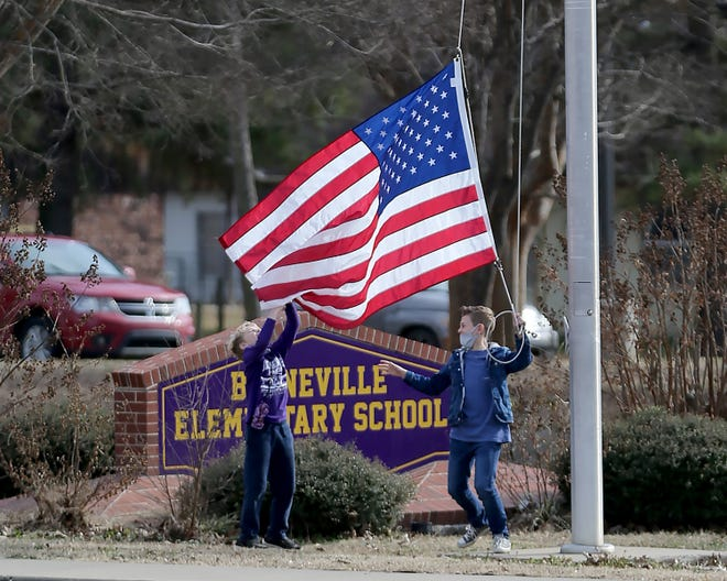 Two boys lower the American flag at the end of the school day, Wednesday, Jan. 13, at the Booneville Elementary School.