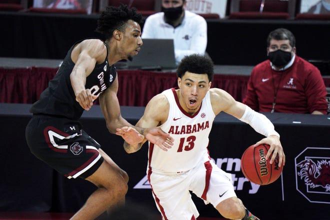 Alabama guard Jahvon Quinerly (13) dribbles against South Carolina guard AJ Lawson (00) during the second half of an NCAA college basketball game Tuesday, Feb. 9, 2021, in Columbia, S.C. Alabama won 81-78. (AP Photo/Sean Rayford)