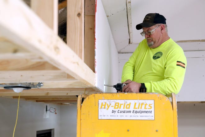 John Manering, a facilities-maintenance technician with the city of Grove City, installs drywall inside the auditorium at the Evans Center, 4330 Dudley Ave., as part of the center's ongoing renovations Feb. 9.