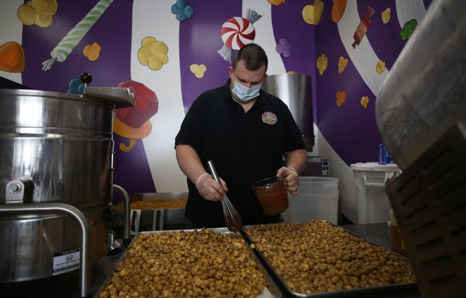 Jeremy Garrett, owner of Fat Baby's Popcorn, drizzles chocolate over the buckeye popcorn Feb. 9  Fat Baby's Popcorn, 1211 Hill Road North, is one of the businesses on the Visit Fairfield County Sweet Tooth Trail.