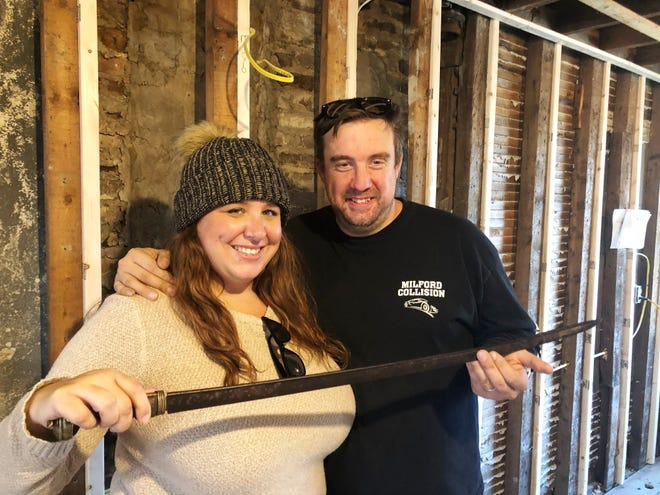 Jaclyn and Gary Manchester hold a saber believed to date to the early 19th century that was found inside a wall of the historic Bellingham house they have been renovating.