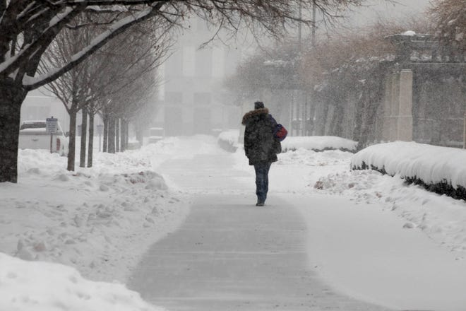A pedestrian walks through the snow at Procter & Gamble Lawn Park in Downtown Cincinnati on Wednesday, Feb. 10, 2021.