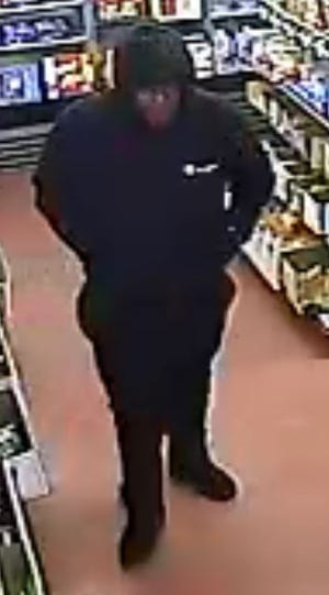 This surveillance photo from the Madeira Beverage armed robbery in which owner Roop  Gupta was shot and killed shows a man last seen fleeing the scene of the shooting in a dark colored vehicle.