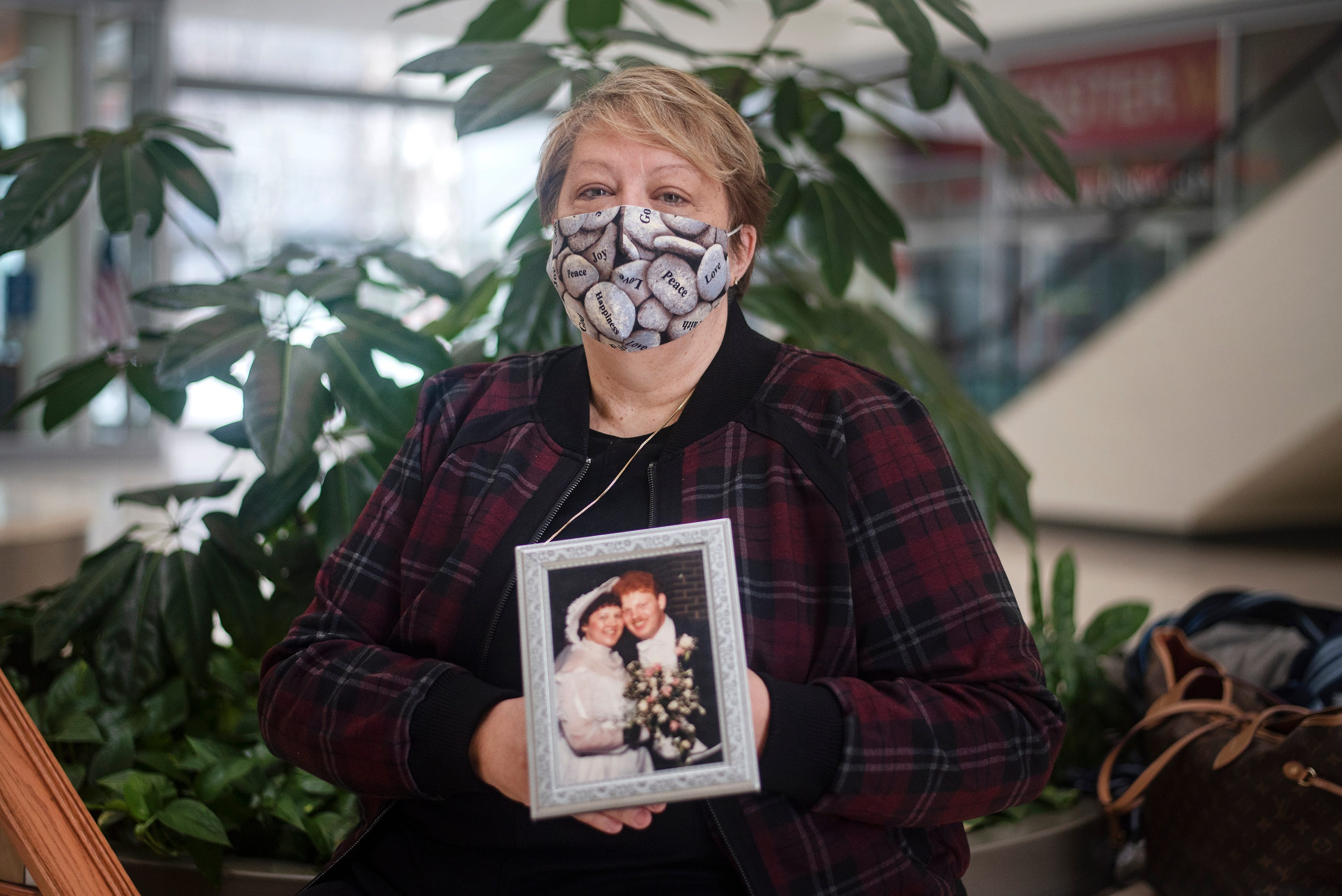 """Lois Vidimos poses with a wedding photo of her late husband Robert Vidimos II. Vidimos II was 58 when he died on Nov. 16, 2020 from complications from COVID-19. """"One of the simplest things that I miss the most is holding his hand,"""" said Vidimos."""