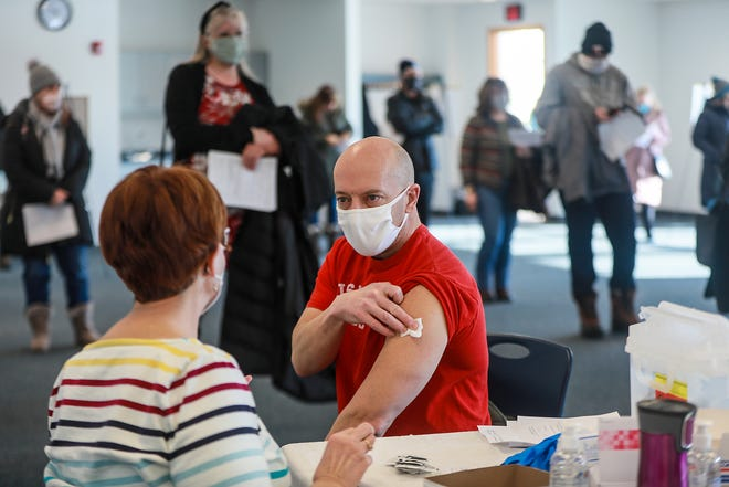 Dave Kadlitz, 50, of Trenton receives the COVID-19 Pfizer vaccine at Wayne County Community College District Downriver Campus in Taylor on Saturday, February 6, 2021. Kadlitz teaches STEM at Southgate Schools.  As many as 2,000 K-12 employees were scheduled to receive vaccines that day as part of the county's first week of vaccination efforts.  The shots were to be given inside the building, but only 300 people could be indoors at one time to still maintain social distance.
