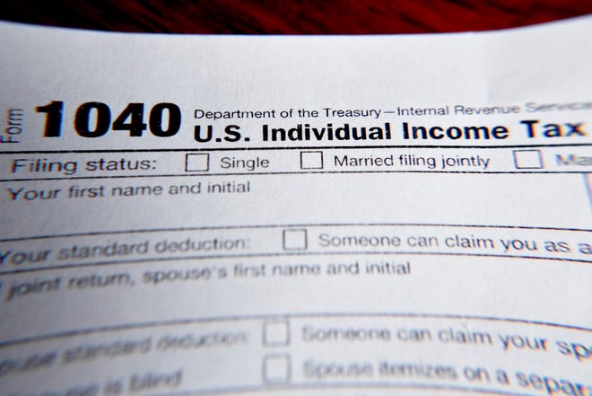 The IRS will begin accepting 2020 federal income tax returns on Feb. 12, 2021. FILE - This 2019 photo shows part of a 1040 federal tax form printed from the Internal Revenue Service website, in Zelienople, Pa.     (AP Photo/Keith Srakocic, File)