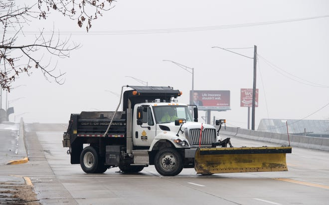 A Kentucky Department of Highways snowplow turns around at the bottom of the overpass on Second Street while spreading salt in the area Wednesday morning, Feb. 10, 2020. A thin layer of ice covered the roads in Henderson County making driving conditions hazardous.