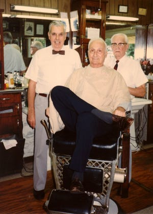 """The Rev. Lyman Smith Allen in a barber chair flanked by Ed Smith, left, and Covington """"Cup"""" Overfield at the Soaper Barber Shop on North Elm Street in the 1980s. Allen preached his first sermon at Immanuel Baptist Temple on Feb. 17, 1946.  (Photo courtesy Ed and Juanita Smith)"""