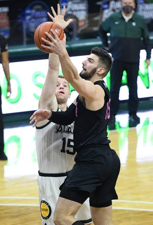 Feb 9, 2021; East Lansing, Michigan, USA;  Penn State Nittany Lions forward Trent Buttrick (15) goes to the basket and is fouled by Michigan State Spartans forward Thomas Kithier (15) during the first half at Jack Breslin Student Events Center. Mandatory Credit: Tim Fuller-USA TODAY Sports