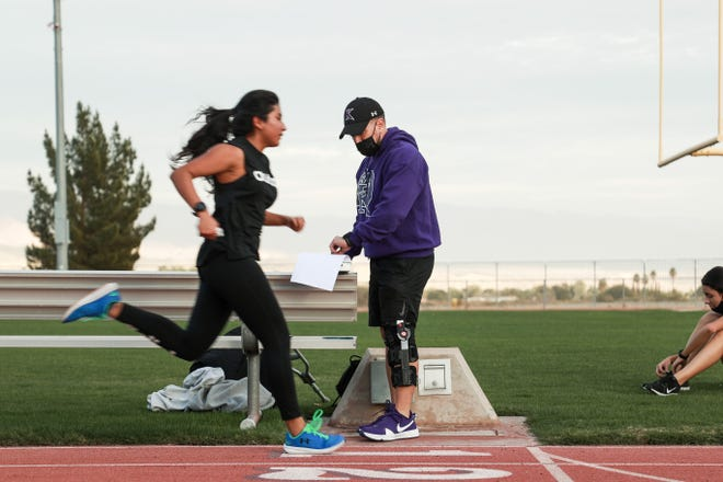 Shadow Hills cross country coach Richie DeTamble records time trials on Tuesday, February 9, 2021, in Indio, Calif. to prepare for a meet on Friday. The meet marks the return of high school sports in the Coachella Valley since the start of the COVID-19 pandemic.