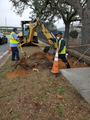City crews perform sidewalk work near St. Michael's cemetery in Pensacola on Wednesday, Feb. 10, 2021. Students participating in city youth council programs will learn about various functions and departments, such as public works crews.
