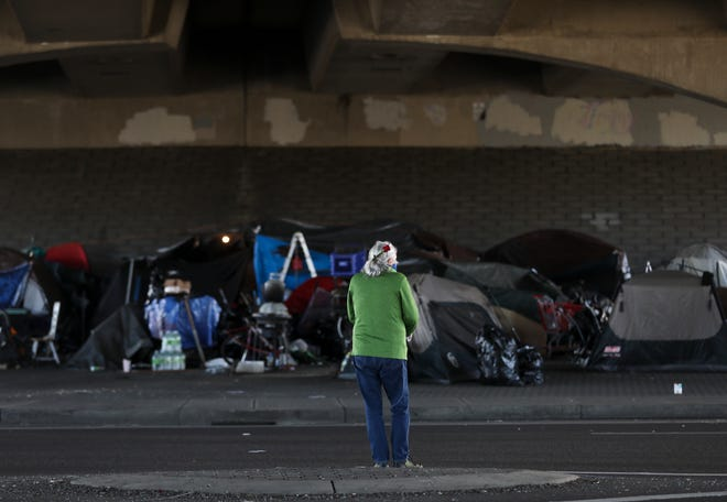 Jolene Garland stands near the homeless encampment near Market Street NE at the Interstate 5 underpass. Garland and other volunteers feed the community every Tuesday.