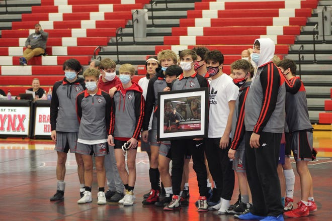 The Brandon Valley wrestling team presents Isaac Klinkhammer with a plaque recognizing his record for career wins.