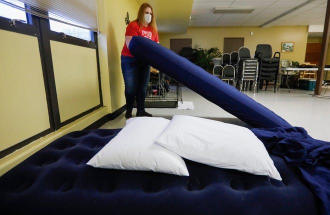 Emily Bowen-Marler, associate minister at Brentwood Christian Church, prepares the church's cold-weather shelter for unsheltered couples and their pets by putting sheets on air mattresses on Wednesday, Feb. 10, 2021.